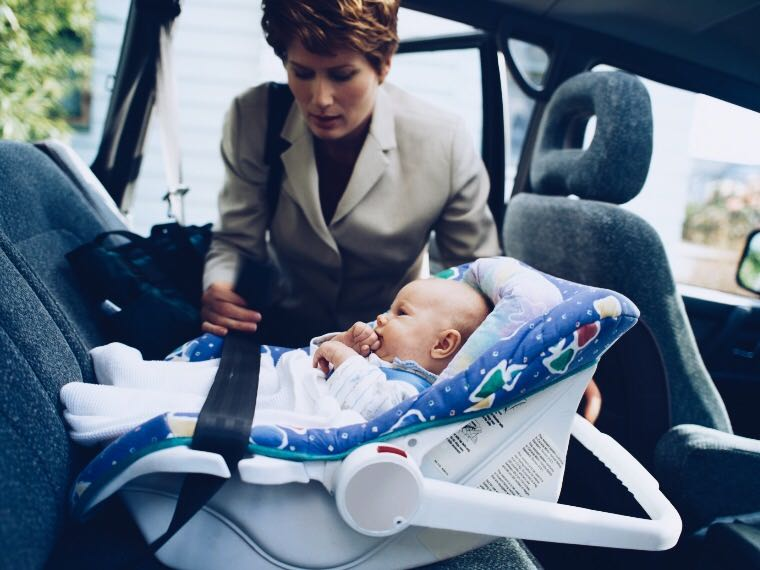 Woman fastening a baby's car seat
