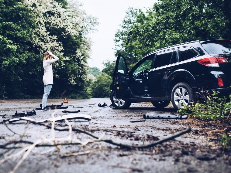 Woman standing next to freshly-wrecked vehicle