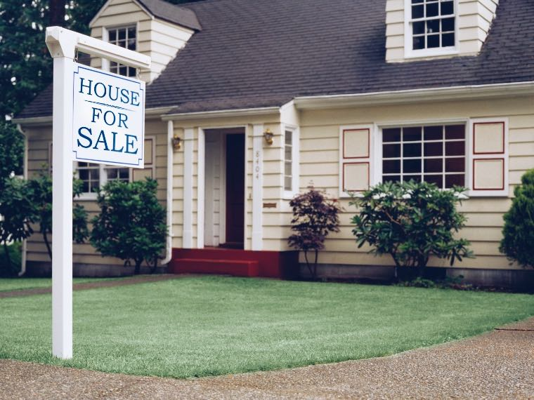 House for sale sign in a front lawn