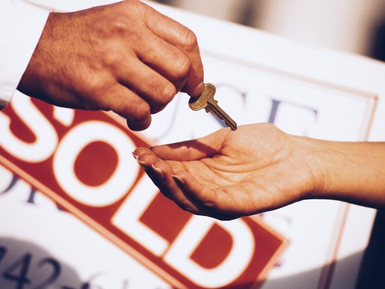 Realtor handing a house key to new homeowner with a sold sign in the background