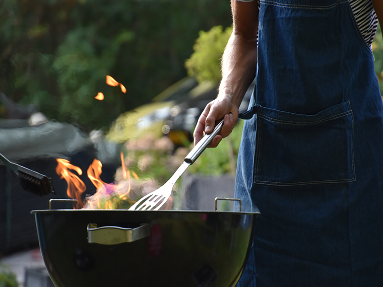 Person grilling on charcoal grill