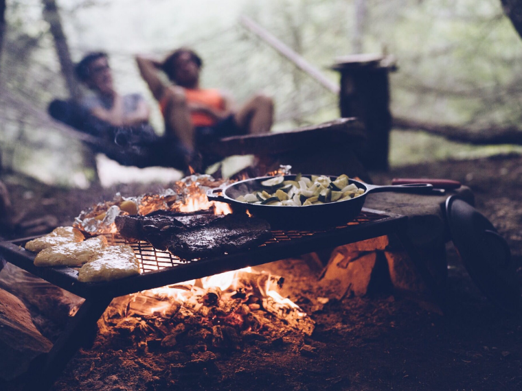 Cooking on top of a campfire while laying in a hammock