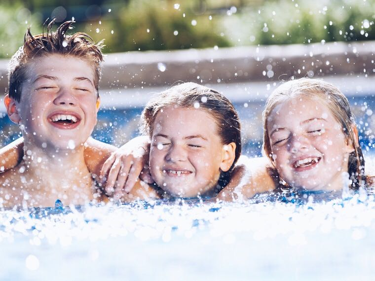 Three children laughing in pool