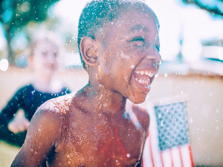 Child playing in water with an american flag in the background